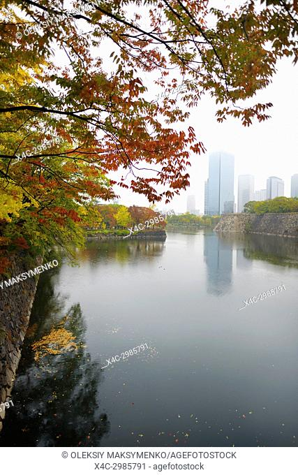 Osaka Chuo-ku financial distric high-rise towers on a misty autumn morning view from Osaka Castle Park inner moat canal in colorful fall scenery