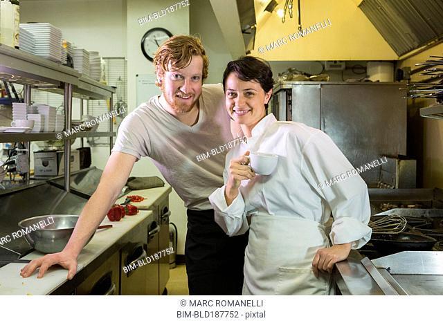 Caucasian chef and waiter smiling in restaurant kitchen