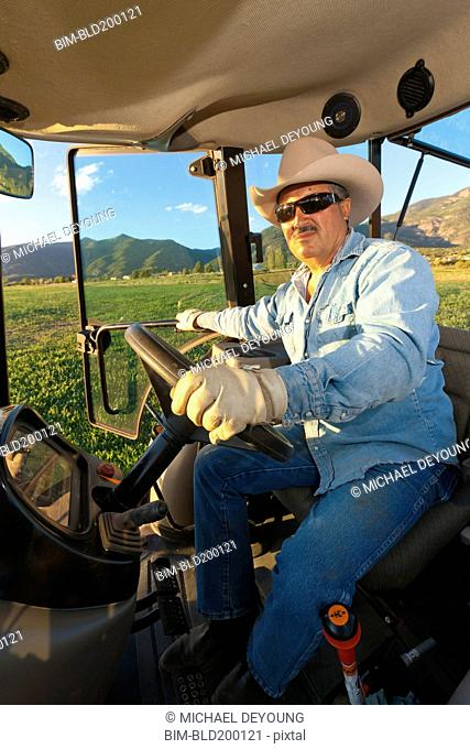 Hispanic man driving tractor