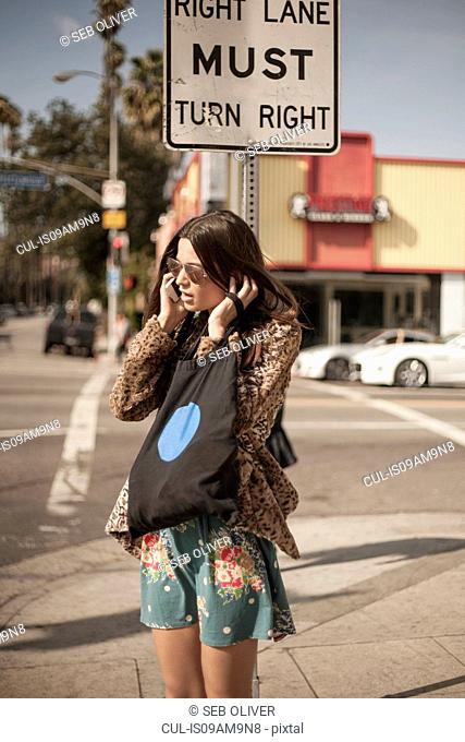 Young woman on corner of street, talking on mobile phone