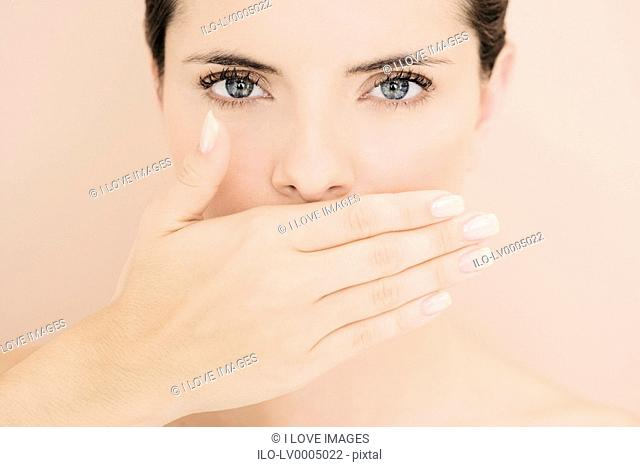 Young woman with hand over her mouth, speak no evil