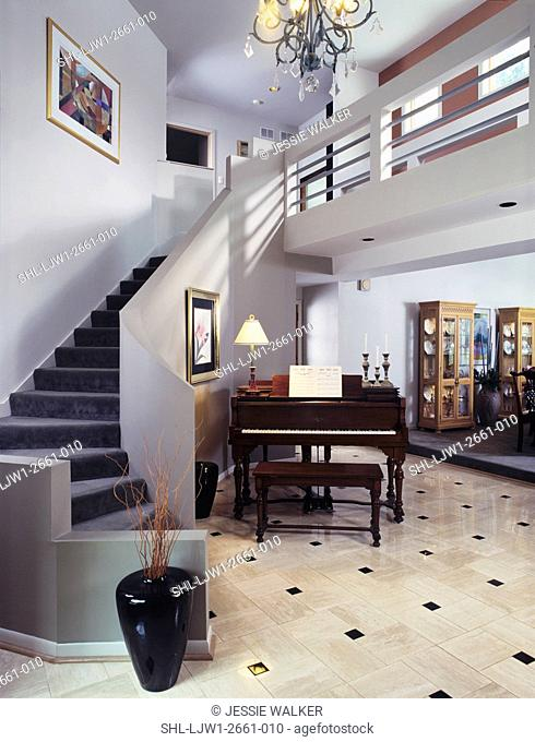 STAIRWAYS: Sleek modern entrance hall with curved carpeted stairs, marble floor, grand piano, dining room off to the right