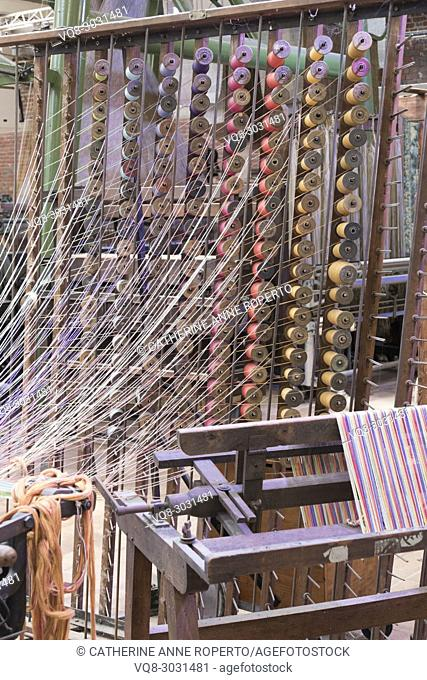Woosh of filmy threads from columns of stacked, brightly coloured wooden bobbins in traditional jacquard weaving manufacture, La Manufacture de Roubaix, France