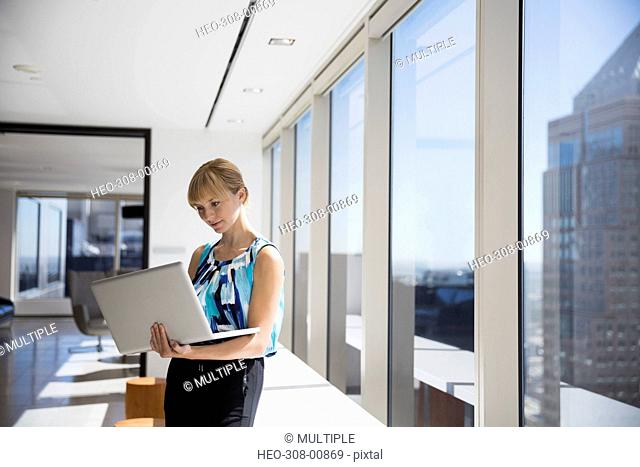 Businesswoman with laptop at sunny urban office window