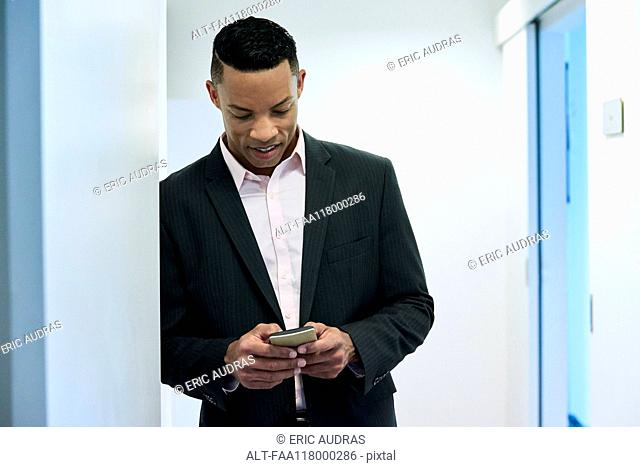 Businessman using smart phone in hotel lobby