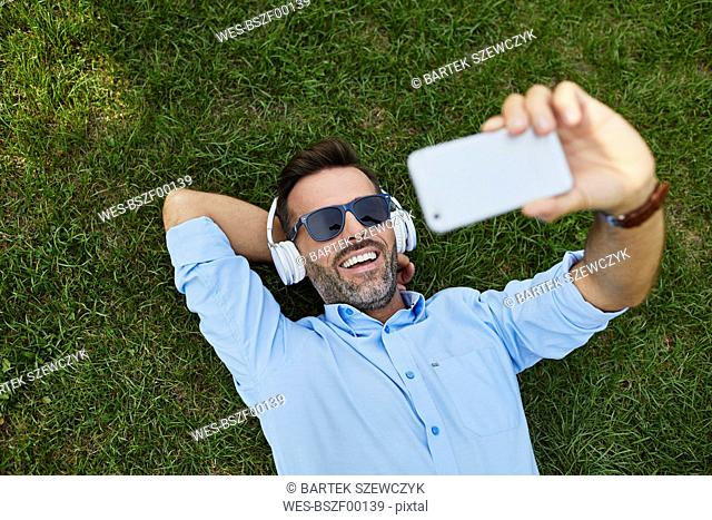 Portrait of laughing man lying on a meadow taking selfie with smartphone, top view