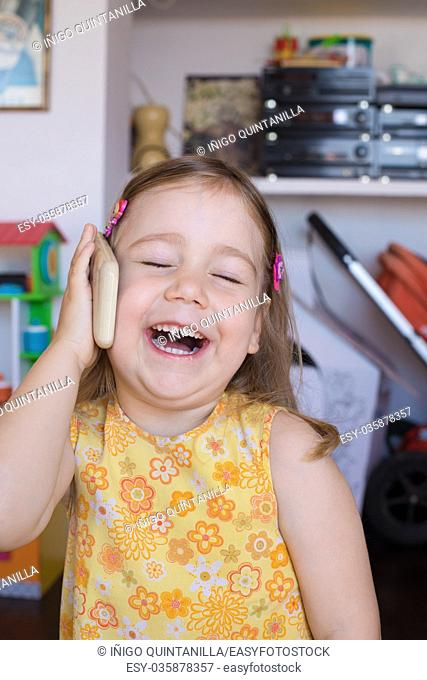 Portrait of three years old child indoors, with yellow dress, talking to smartphone mobile in her hand in ear, laughing with happy expression face