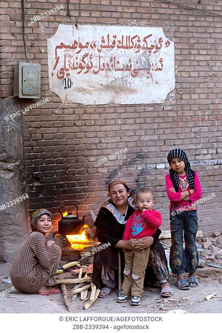 Uyghur Family making fire in the street, Kashgar, Xinjiang Uyghur Autonomous Region, China