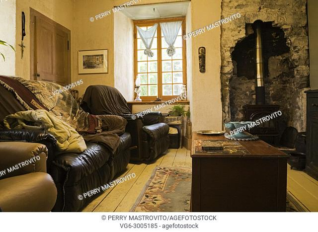 Draped leather sofas and trunk coffee-table in the living room inside an old Canadiana (1840s) fieldstone cottage style residential house, Quebec, Canada