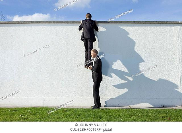 Businessman lifting colleague over wall