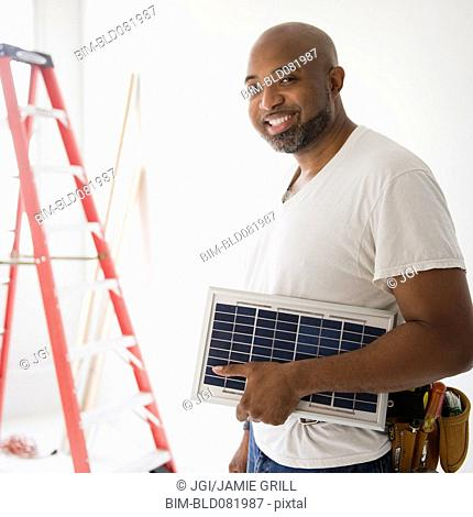 African American construction worker carrying solar panel
