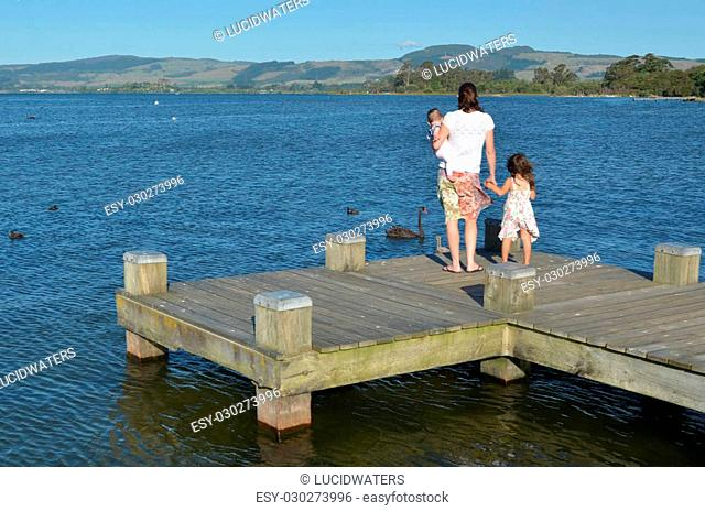 Mother with two children (girls age 5 and baby 01) stand on a jetty and looks at Black swans on Lake Rotorua waterfront, New Zealand