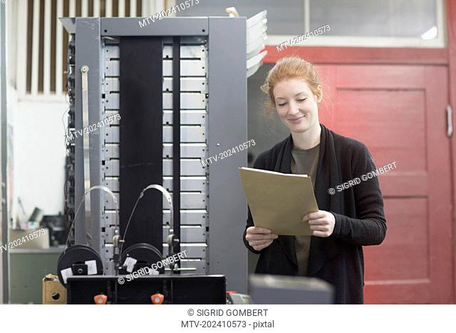 Smiling woman standing by printing press machine and holding document