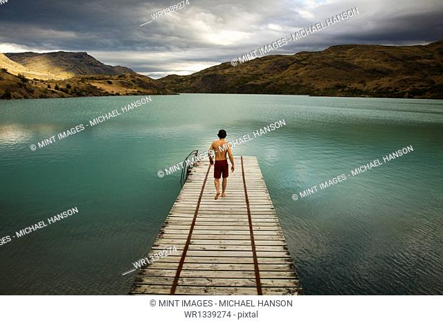 A young man walking down a wooden pier, towards calm lake surrounded by mountains in Torres del Paine National Park, Chile
