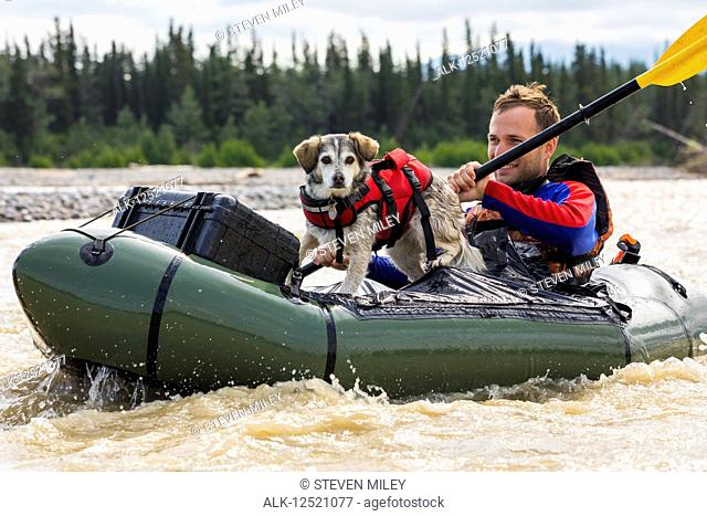 Man with his dog in a pack raft in Jarvis Creek, Interior Alaska; Alaska, United States of America