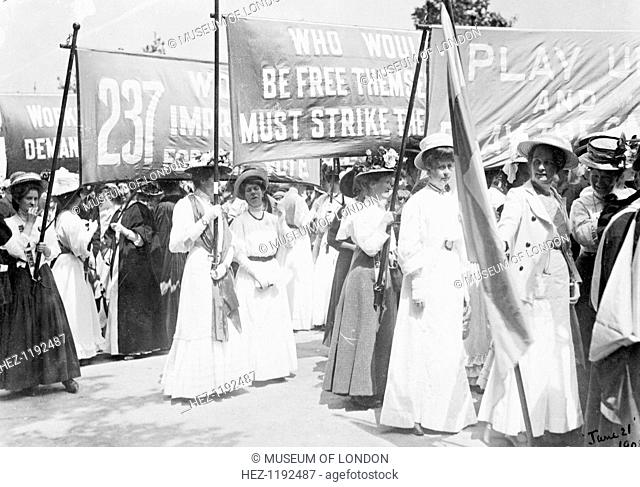 Suffragettes on the Euston Road procession carrying banners to Women's Sunday, London, 21st June 1908. The marching women were accompanied by drums and bugles