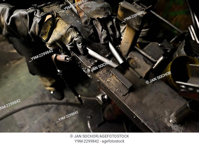A bicycle welder fixes metal tubes on a welding jig in a small scale bicycle factory in Bogota, Colombia, 10 April 2013. Due to the strong