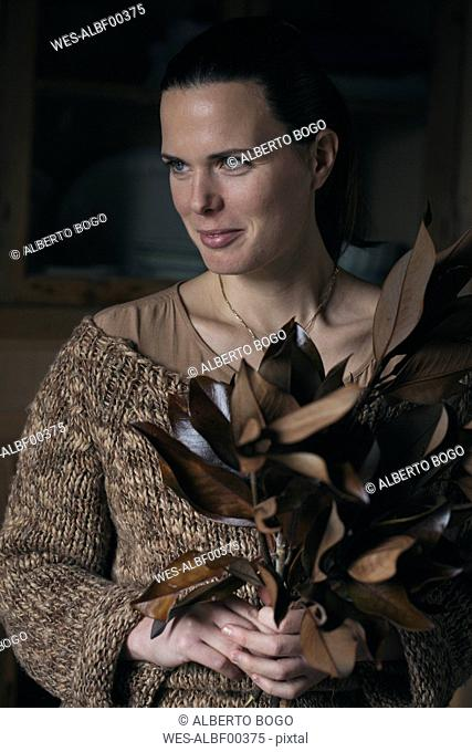 Portrait of smiling woman with bunch of twigs with brown leaves