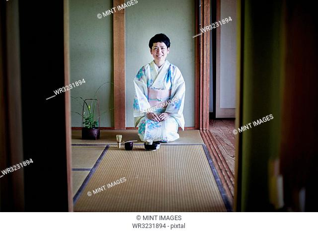 Japanese woman wearing traditional white kimono with blue floral pattern kneeling on tatami mat during tea ceremony