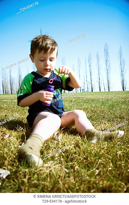 Young boy blowing bubbles in the park