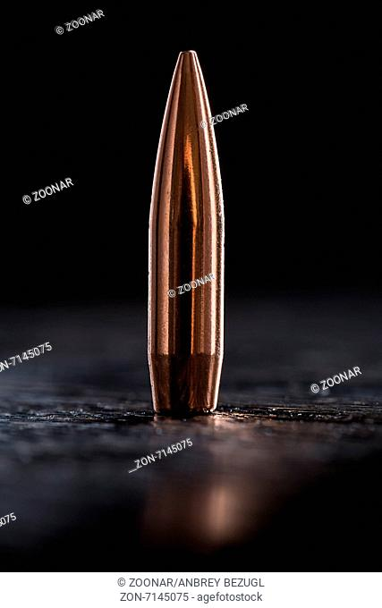 One copper bullet with bright reflections on a black background