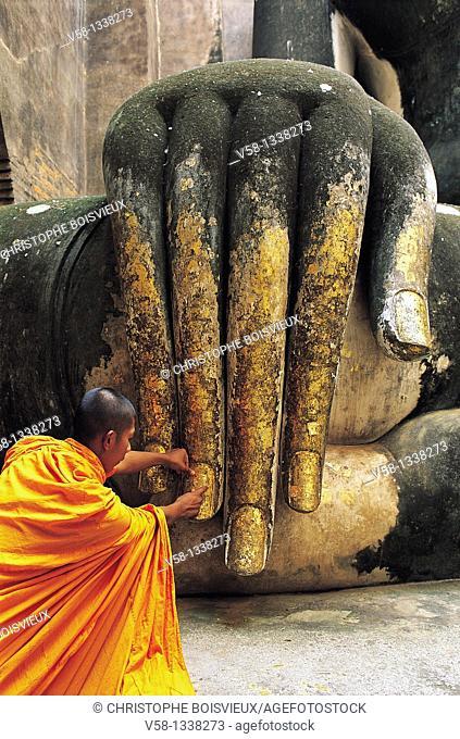 BUDDHIST MONK APPLYING GOLD LEAVES ON BUDDHA'S HAND, WAT SI CHUM, SUKHOTHAI, THAILAND