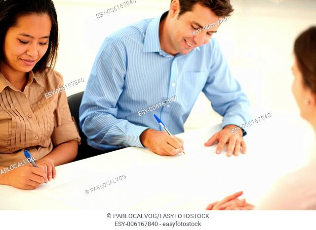 Portrait of male and female worker signing a contract while smiling and sitting on office desk
