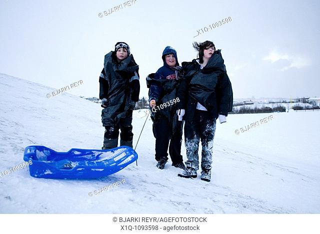 Three boys posing for camera in snow, Hafnarfjordur Iceland