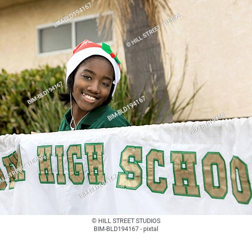 Mixed race student holding high school banner