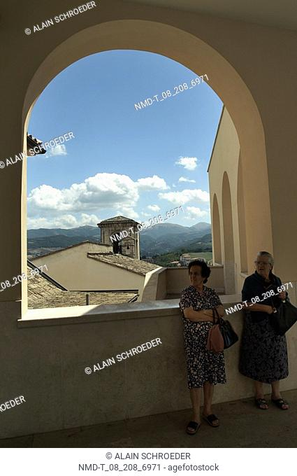 Senior woman and a mature woman standing in front of a window, Cascia, Umbria, Italy