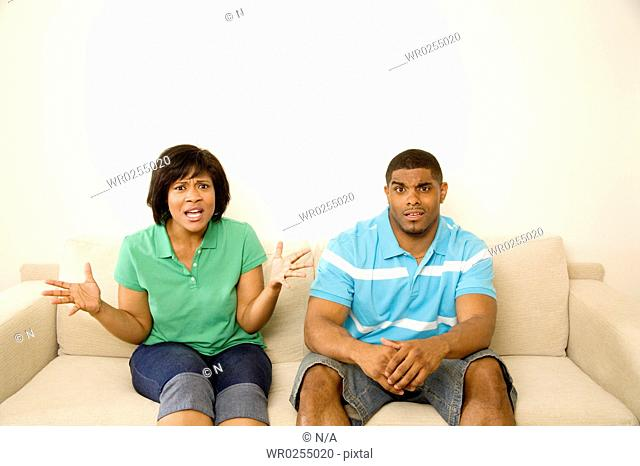 Confused couple sitting on a couch