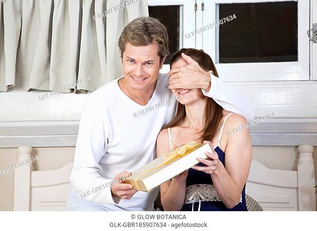 Man obscuring woman's eyes with hand and giving present
