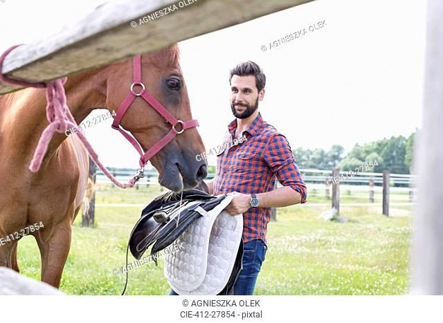 Man removing saddle from horse in rural pasture
