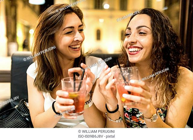 Young women enjoying cocktail on night out