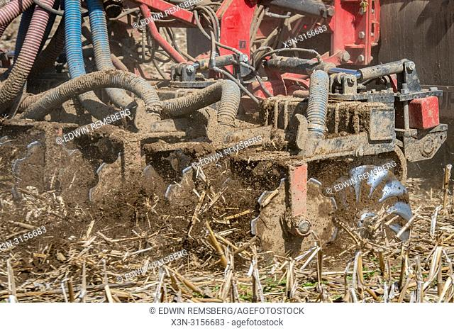 A tractor driven tanker injects duck manure into corn stubble to help fertilize the crops near Hagerstown, Maryland