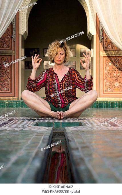 Morocco, Marrakesh, tourist sitting on the floor doing yoga