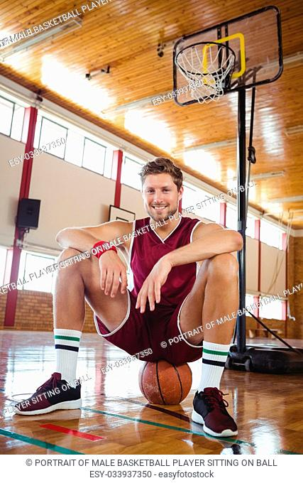 Portrait of male basketball player sitting on ball against hoop in court