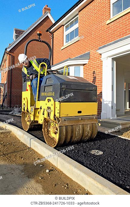 Hard landscaping in progress on a new residential development in South East England. Man driving a roller on asphalt pavement