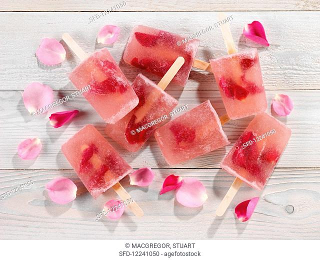 Several rose petal ice-lollies with rose petals on a wood background