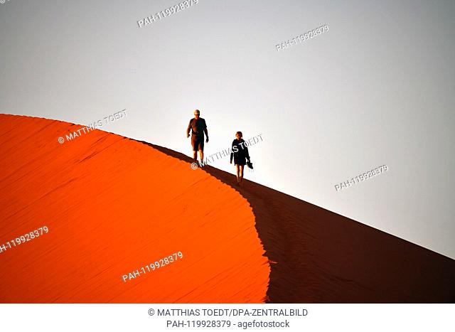 Tourists descend from one of the dunes in Sossusvlei, taken on 01.03.2019. The Sossusvlei in the Namib-Naukluft National Park has been a UNESCO World Heritage...