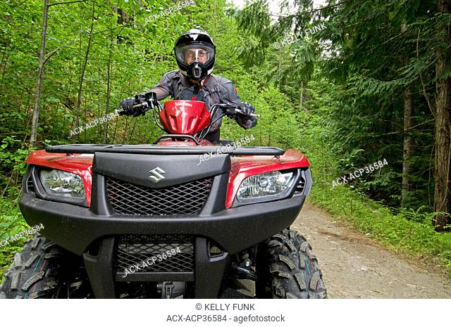 A single male ATV quad rider makes his way down the trail near Powell river on the upper Sunshine coast, Vancouver coast and mountain range, British Columbia