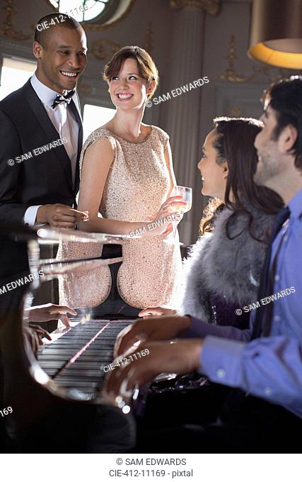 Well dressed friends playing piano in lounge