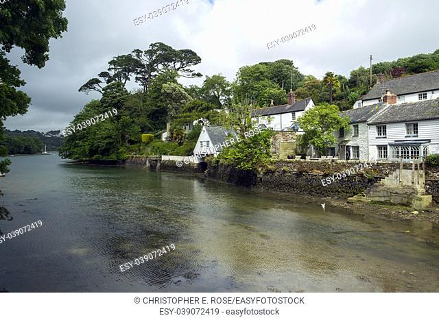 Picturesque old cottages line the waters edge in Helford village on the Helford Estuary in Cornwall, UK