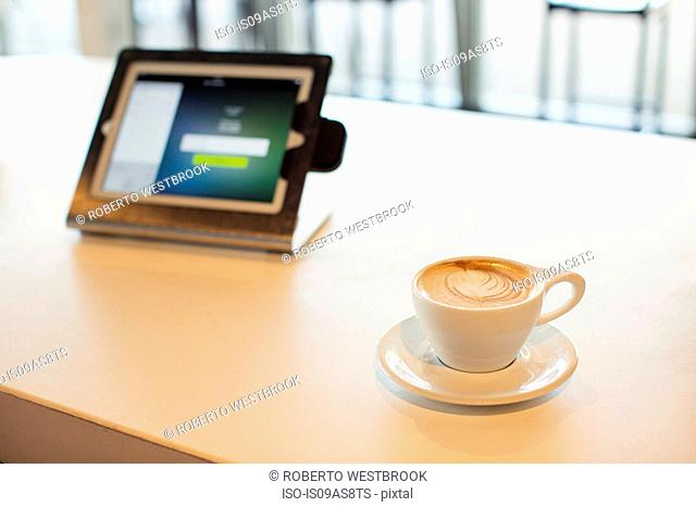 Cup of coffee and digital tablet on table in coffee shop, still life