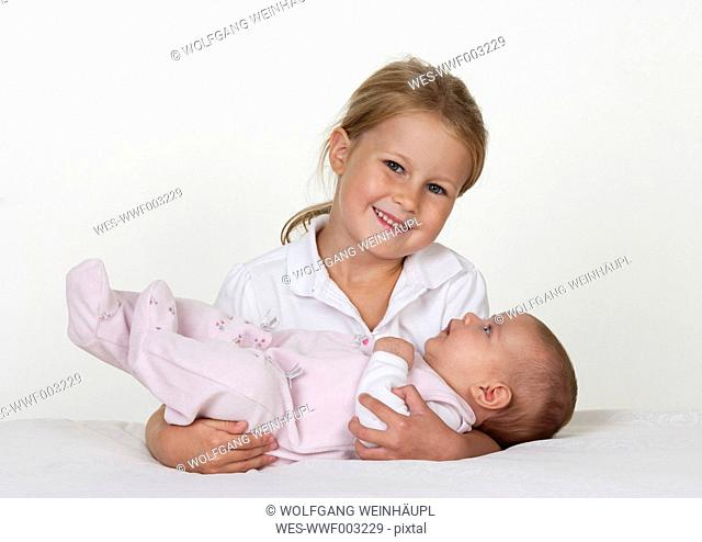 Portrait of smiling little girl holding newborn sister