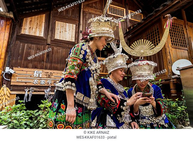 China, Guizhou, three Miao women wearing traditional dresses and headdresses using cell phone