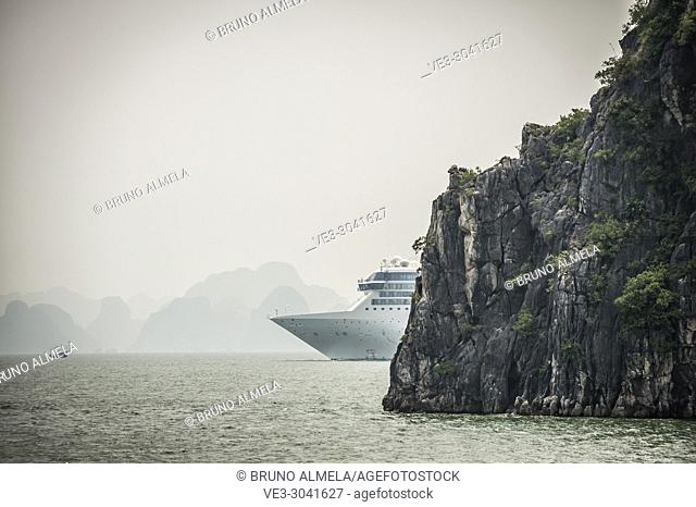 Tourists ocean cruiser in the karst landscape of Ha Long Bay, Quang Ninh Province, Vietnam. Ha Long Bay is a UNESCO World Heritage Site