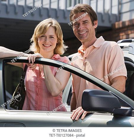 Couple standing in car door