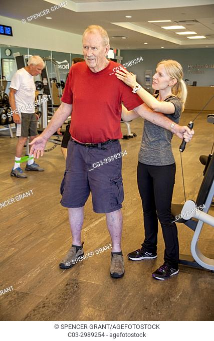 A young adult instructor helps a senior man with a workout in the gymnasium of a senior center in Huntington Beach, CA
