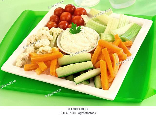 Raw vegetables on a platter with herb dip